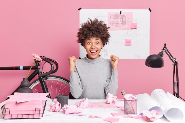 Feliz, jovem mulher afro-americana, engenheira cerrada os punhos, desfruta de ótimos resultados no processo de trabalho, comemora poses de sucesso na mesa do escritório trabalha em planos técnicos