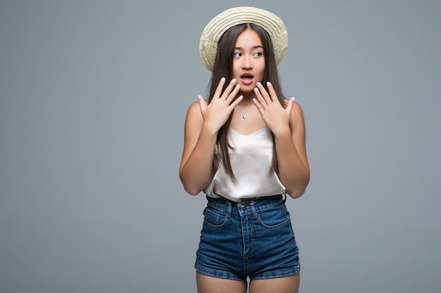Feliz jovem mulher asiática chocada isolada em fundo cinza