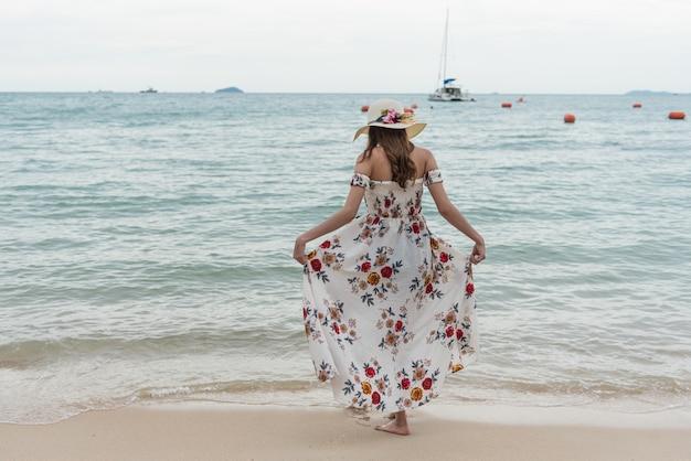 Feliz jovem mulher asiática com chapéu andando e relaxando na praia de areia