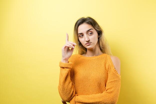 Feliz jovem mulher branca com um suéter amarelo, apontando os dedos para longe.