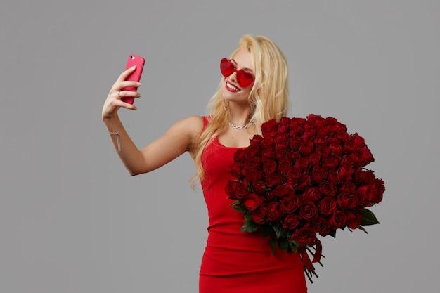 Feliz jovem mulher loira de óculos de forma de coração segurando um grande buquê de rosas vermelhas e telefone móvel