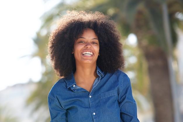 Feliz jovem negra fora por palmeiras sorrindo