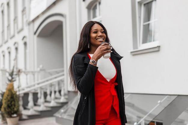 Feliz jovem negra na moda terno vermelho no casaco longo da moda com uma xícara de café caminha e sorrindo na rua perto do edifício vintage. menina elegante positiva africana com sorriso fofo na cidade.