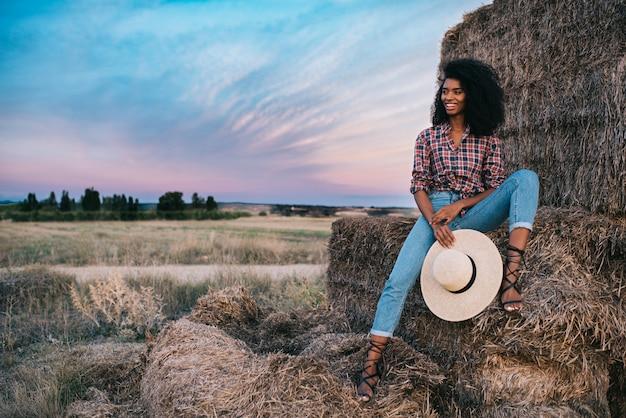 Feliz jovem negra sentada sobre uma pilha de feno