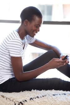 Feliz jovem negra usando celular pela janela dentro de casa