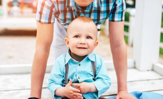 Feliz jovem pai com filho pequeno se divertir ao ar livre no parque