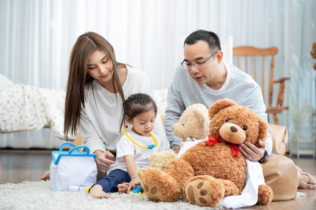 Feliz jovem pai e mãe e uma filha brincando com toy, sentado no chão na sala de estar, família, paternidade e conceito de pessoas