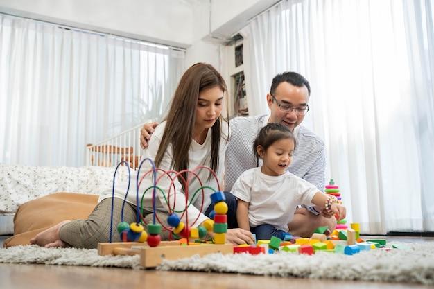 Feliz jovem pai e mãe e uma filha brincando