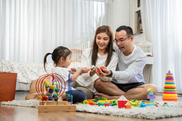 Feliz jovem pai, mãe e uma filha brincando com blocos de madeira de brinquedo, sentados no chão na sala de estar, família, paternidade e conceito de pessoas com brinquedos de desenvolvimento