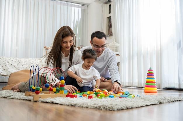 Feliz jovem pai, mãe e uma filha brincando com blocos de madeira de brinquedo