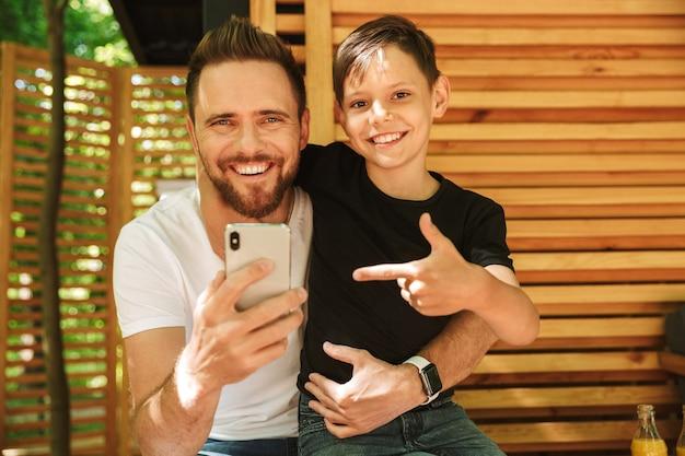 Feliz jovem pai sentado com seu filho, usando o telefone móvel apontando.