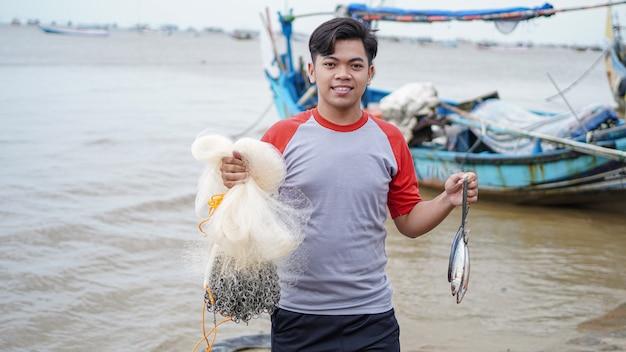 Feliz jovem pescador na praia segurando sua pescaria e shows na frente de seu barco