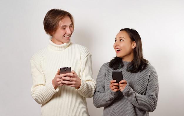 Feliz jovem rapaz e rapariga com smartphones na mão, conversando e rindo. em branco