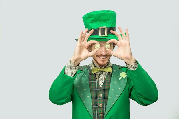Feliz jovem rico em terno verde segura duas moedas de ouro na frente dos olhos. ele sorri e parece feliz. cara usa traje verde de são patrício. isolado em cinza.