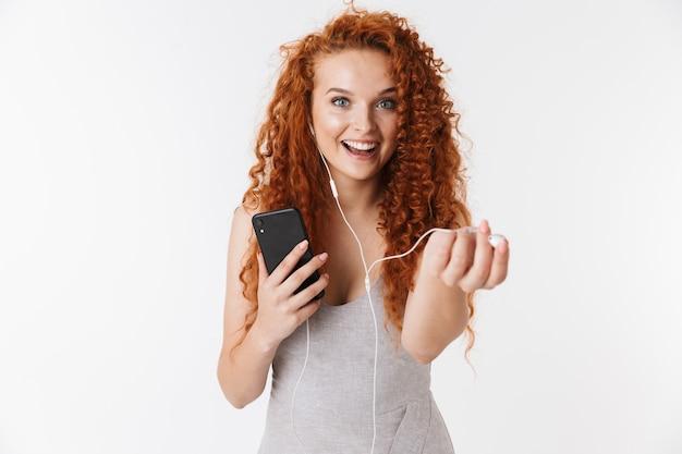 Feliz jovem ruiva encaracolada usando telefone celular ouvindo música.