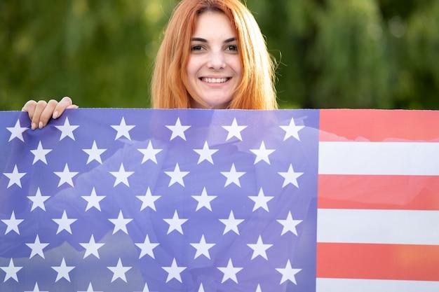 Feliz jovem ruiva posando com a bandeira nacional dos eua em pé ao ar livre no parque de verão.