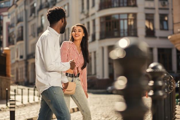 Feliz jovem sorrindo para o namorado e andando na rua em um dia ensolarado com ele