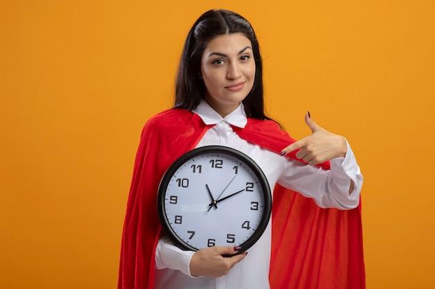 Feliz jovem super-heroína caucasiana segurando e apontando para o relógio, olhando para a câmera isolada em um fundo laranja com espaço de cópia