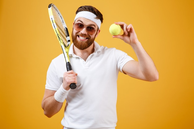 Feliz jovem tenista mostrando a bola de tênis.
