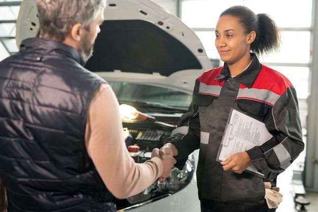 Feliz jovem trabalhador contemporâneo de serviço de carro com documento técnico apertando a mão de um cliente do sexo masculino contra a parte dianteira de um carro quebrado