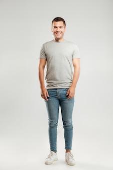 Feliz jovem vestido com camiseta cinza isolada sobre parede cinza