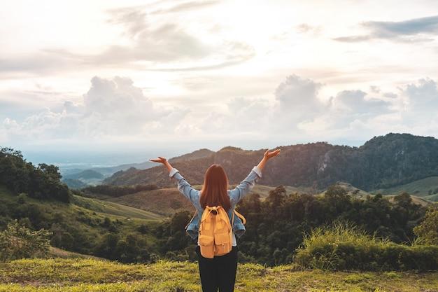 Feliz jovem viajante relaxando e olhando o belo pôr do sol no topo da montanha
