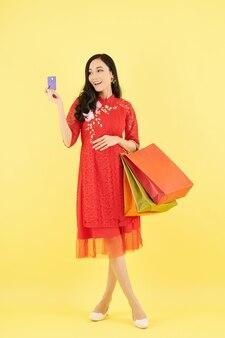 Feliz jovem vietnamita com vestido de renda vermelha segurando sacolas de papel e olhando para o cartão de crédito na mão