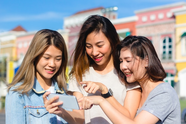 Feliz, jovens mulheres asiáticas, grupo, cidade, estilo vida, tocando, e, conversando, um ao outro