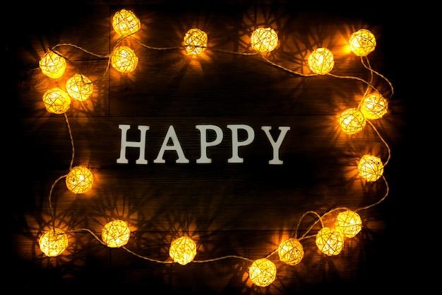 Feliz, letras de papel no escuro com lâmpadas