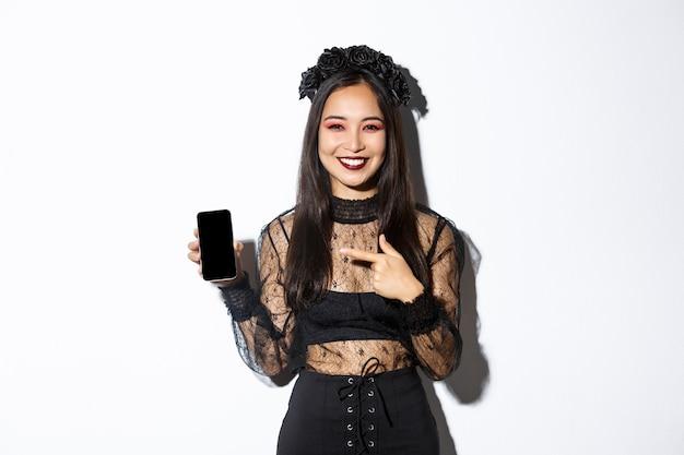 Feliz linda garota asiática na fantasia de bruxa, apontando o dedo para a tela do smartphone com um sorriso satisfeito, mostrando o anúncio de halloween, fundo branco.