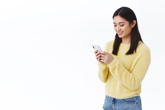 Feliz linda garota asiática usando telefone celular e sorrindo. aluna enviando meme engraçado via messanger de mídia social, bate-papo com amigos ou membros da equipe, videochamada no smartphone, parede branca