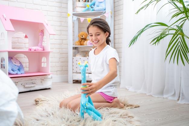 Feliz linda garota brincando no quarto dos filhos em um brinquedo feito de girafa de tecido.