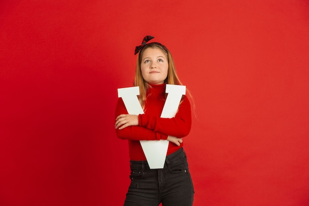 Feliz, linda garota caucasiana segurando a carta no fundo vermelho do estúdio. conceito de emoções humanas, expressão facial, amor, relações, férias românticas.