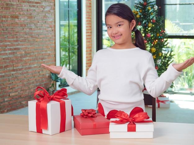 Feliz linda garota com caixas de presente em casa com decorações festivas. feliz natal feliz ano novo.