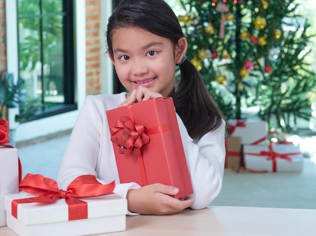 Feliz linda garota com caixas de presente em casa com decorações festivas.