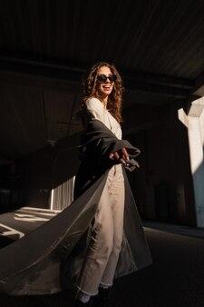 Feliz linda garota de cabelos cacheados com um sorriso em um casaco longo elegante e roupas bege caminha na rua em um fundo de um fundo escuro urbano. modelo de mulher elegante e engraçada