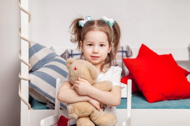 Feliz linda garota de três anos sentada no quarto de seus filhos e abraços de ursinho de pelúcia. adorável criança sortuda com ursinho de pelúcia na cadeira em casa e olhando para a câmera. momentos atmosféricos em família para o bebê