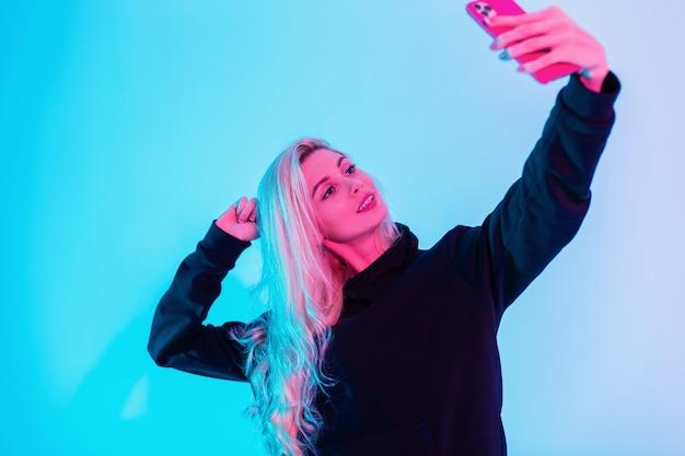 Feliz linda garota jovem e sorridente com um rosto bonito em um capuz preto da moda faz uma selfie no telefone no estúdio com luzes de néon rosa criativas