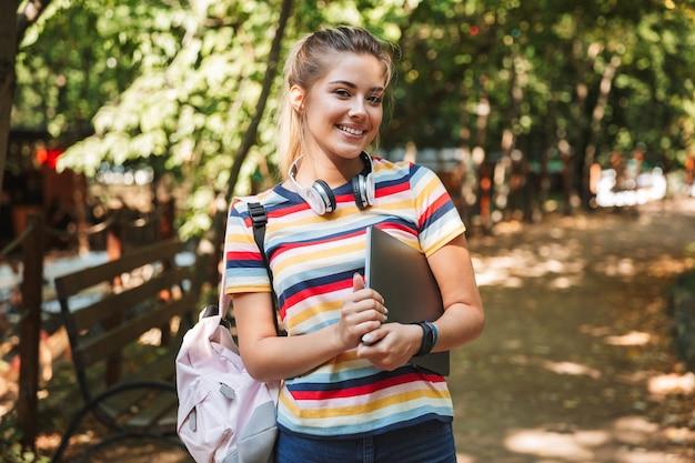 Feliz linda garota jovem no parque ao ar livre segurando o laptop.