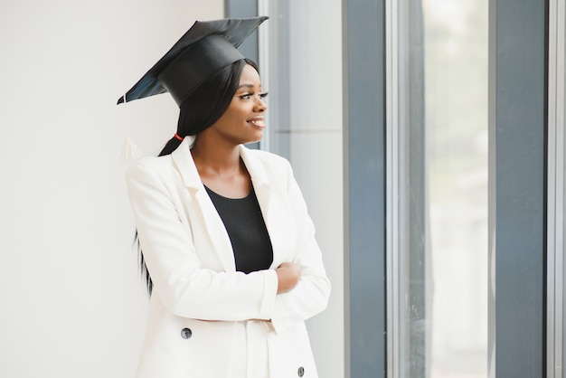 Feliz linda garota negra afro-americana com chapéu de graduados
