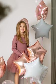 Feliz linda garotinha segurando balões em forma de estrelas. festa de aniversário. rosto bonito criança caucasiana 6-7 anos