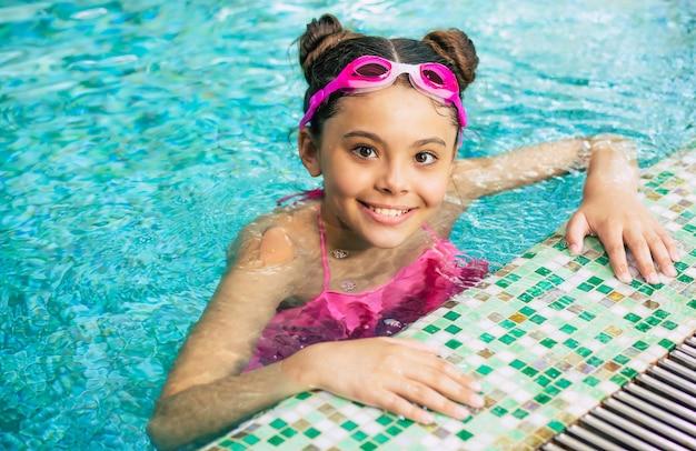 Feliz linda garotinha sorridente de óculos e maiô na piscina se diverte durante as férias ou aulas de natação.