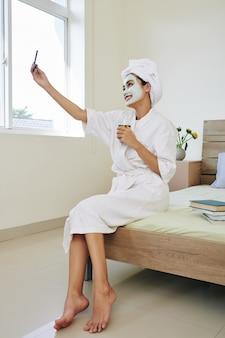 Feliz linda jovem asiática em roupão de banho, sentada na beira da cama com máscara retexturizante no rosto, bebendo chá verde e tomando selfie.
