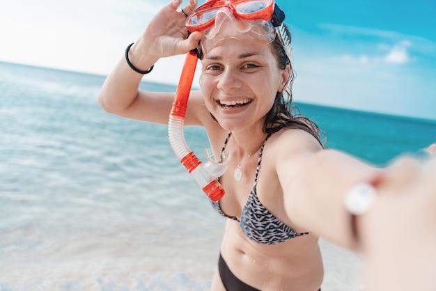 Feliz linda jovem encantadora com um lindo sorriso de biquíni em uma máscara para mergulho leva uma selfie à beira-mar, atividades ao ar livre, atividades de praia