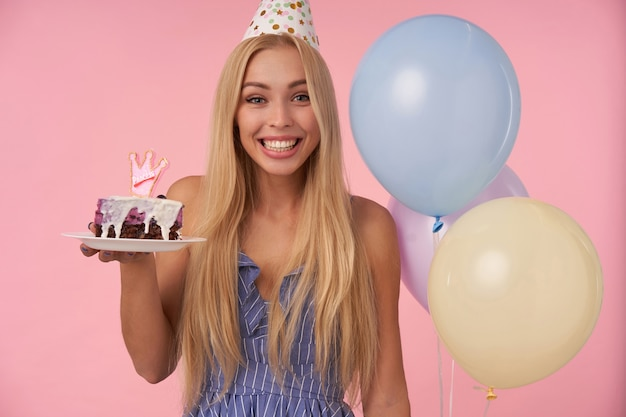 Feliz linda jovem loira com cabelo comprido, tendo momentos alegres em sua vida durante a festa de aniversário, usando roupas festivas e chapéu de cone, em pé sobre um fundo rosa com um pedaço de bolo
