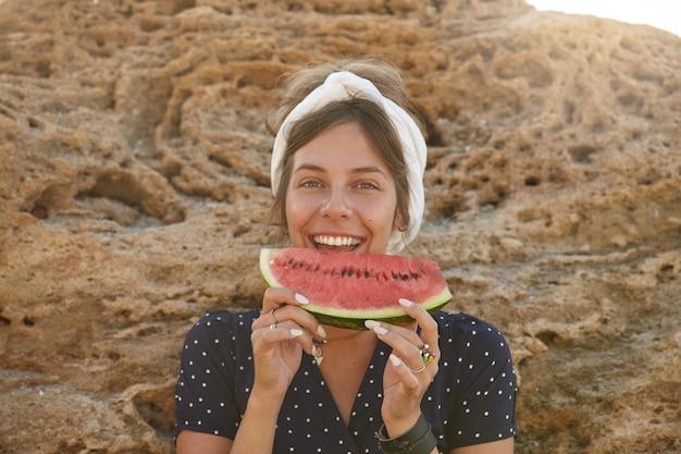 Feliz linda jovem morena de cabelos escuros com bandana e penteado casual posando sobre uma grande pedra amarela em um dia quente de sol, comendo melancia e olhando alegremente