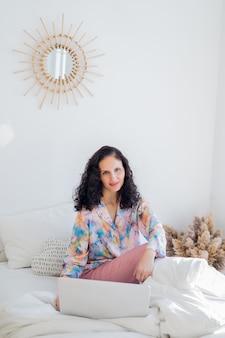 Feliz linda jovem morena trabalhando em um laptop enquanto está sentado na cama no quarto, trabalhando em trabalho freelance online. o conceito de trabalhar em um computador em casa