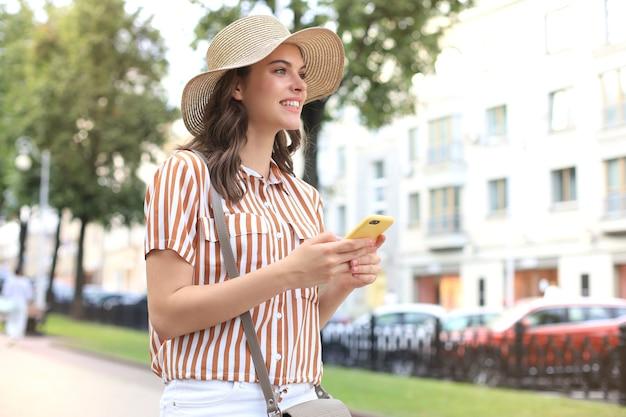 Feliz linda jovem morena usando telefone celular enquanto caminha ao ar livre.