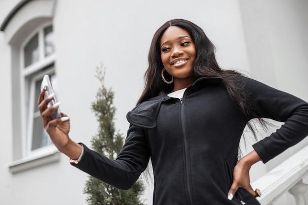 Feliz linda jovem negra africana em roupas da moda com telefone celular na cidade