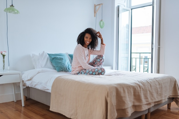 Feliz linda jovem negra relaxado sentado na cama